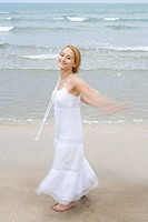 Young woman standing on beach, smiling, portrait