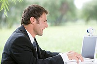 One mid adult man using laptop in lawn, smiling
