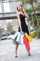 Teenage girl holding shopping bags using mobile phone