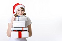 Teenage girl wearing Santa hat holding stack of gifts, smiling, portrait
