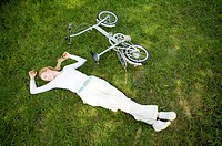 Young woman lying on the lawn with a bicycle