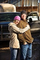 Young Caucasian couple embracing with truck in background.