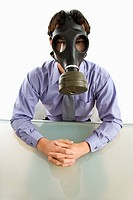 Businessman sitting in white room wearing gas mask