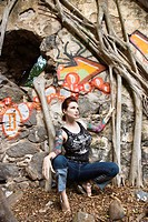 Sexy Caucasian tattooed woman crouching next to wall covered in graffiti and Banyan tree branches.