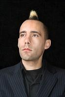 Portrait of Caucasian man in suit with mohawk against black background.