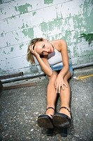 Caucasian mid_adult blonde woman sitting against wall of building with head in hand and looking at viewer.