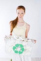 woman carrying rubbish bin