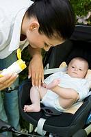 Mother applying cream on baby\´s legs