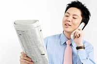 Businessman calling with cell phone and watching a newspaper