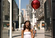 Woman with red baloon in city center