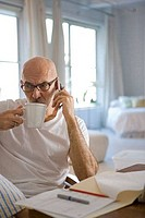 Mature man drinking a cup of coffee and talking on a mobile phone