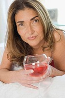 Close_up of a mature woman lying on the bed and holding a glass of wine