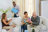Man holding a gift with his three friends sitting on a couch