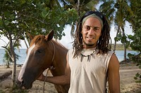 Hispanic man leading horse near beach