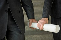Close_up of two hands holding rolled up paper