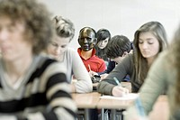 Classroom full of students working, one in middle with mask on