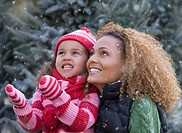 Mixed race mother and daughter watching snow fall