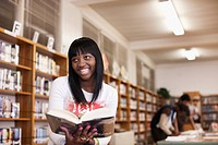 African teenage girl reading in school library