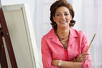 Hispanic woman sitting with canvas on easel