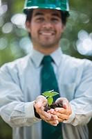 Hispanic business man holding seedling in hands