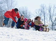 African man pushing children downhill on sled