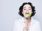 woman holding fork with leaf of salad