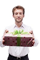Young man holding gift box, portrait