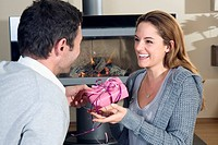 Young couple, man handing over gift to woman, smiling