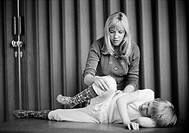 Seventies, black and white photo, people, physical handicap, physiotherapist makes gymnastic exercises with a young boy, aged 25 to 30 years, aged 3 t...