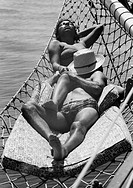 Seventies, black and white photo, people, freetime, sexuality, boat ride on the Atlantic Ocean near Rio de Janeiro, young girl and young man in swimwe...