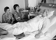 Eighties, black and white photo, people, health, older woman lies in a sickbed of a hospital, two women visit her sitting beside the bed, aged 70 to 8...