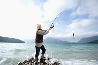 Germany, Bavaria, Walchsensee, Senior woman fishing in lake
