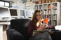 Businesswoman in office holding cup of coffee, portrait