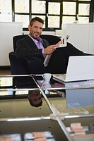 Business man in office holding newspaper, portrait