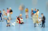 Wheelchair_bound man figurine among people, close up