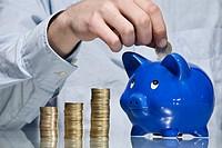 Person putting Euro coin into piggy bank