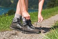 Austria, Lake Mondsee, Person tying shoe