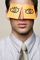 Young business man with orange post_it notes covering eyes with drawn on cartoon eyes