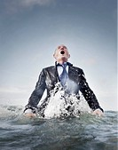 a businessman coming out of the sea for air, struggling.