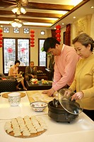 Chinese mother and her son making Chinese dumpling on New Year´s Eve