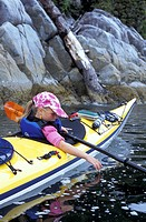 Young girl dips her hand in water while kayaking with her family in The Broken Group Islands, British Columbia