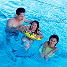 Girl 6_8 sitting in inflatable ring with parents in swimming pool