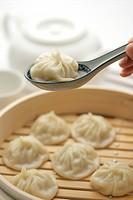 Chinese dumplings on soup spoon