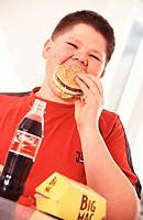 Thick boy eating a hamburger