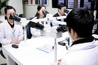 Four laboratory technicians using microscope