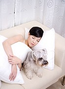 Young woman sleeping on sofa with a Wire Fox Terrier, elevated view