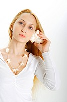 Young woman holding seashell to ear
