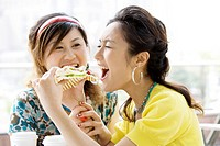 Young woman stopping her friend eating hamburger, smiling, portrait