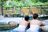 Young women with towel bathing in hot spring, rear view