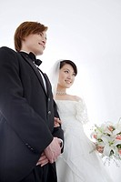 Bride and groom standing arm in arm